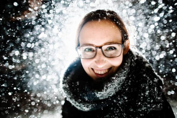 woman smiles at the camera at night with snow all around he