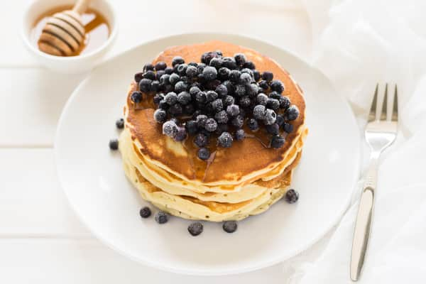 Stack of pancakes with frozen blueberries and honey on white wooden table. Selective focus