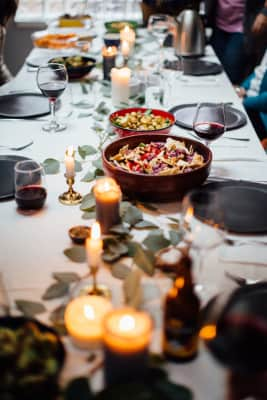 A salad sits on a long table for a big family birthday celebration with wine, candles, beer and a centerpiece of leaves.