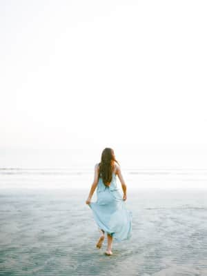 Young woman on the beach wearing a beautiful blue dress. Running towards the ocean.  Fine art style and shot on film.