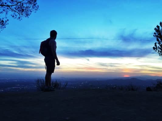 Man silhouette overlooking the city of Los Angeles while on a hike.