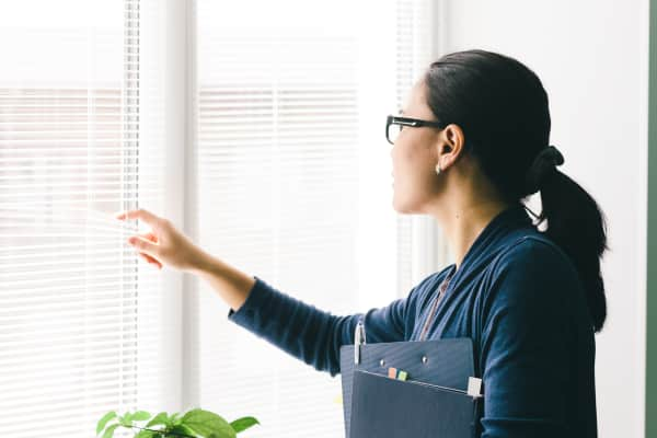 Girl office worker looking out the window through blinds