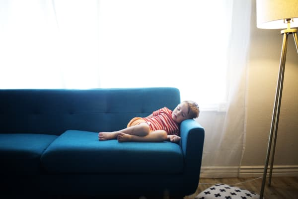 Boy asleep for a nap in a blue couch at home