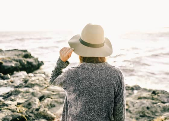 Woman at a rocky beach holding her hat