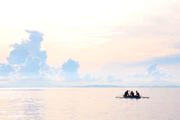 Three men and a boat with the luxurious view of sunset.
