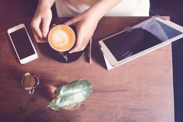 Top view of woman hands holding hot latte coffee with tablet and smartphone on wooden table in the cafe