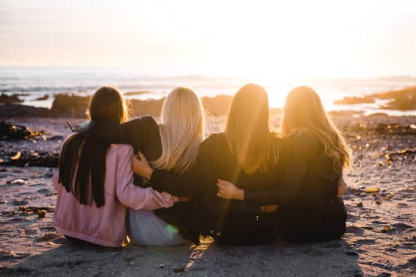 Girls sitting on beach watching sunset
