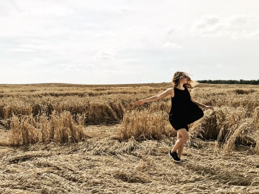 Happy young woman dancing in field.
