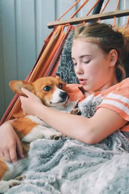 Girl talking to her dog in the hammock