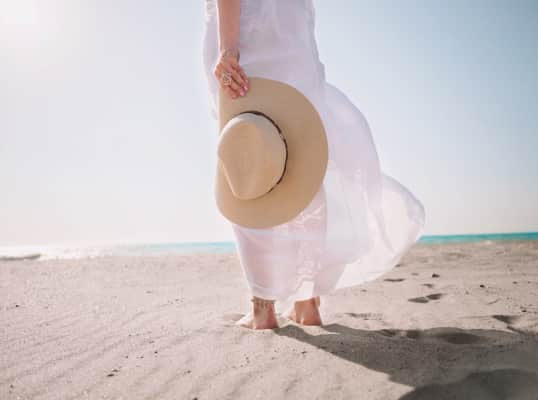 Portrait of beautiful woman in white dress and hat in hand walking on beach near sea or ocean