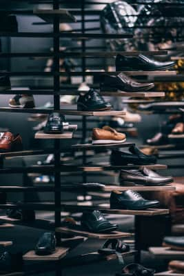 Men's shoes are on display in a shop for sale.