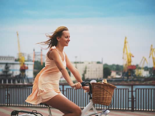 Beautiful young blonde woman riding retro bicycle in marine port