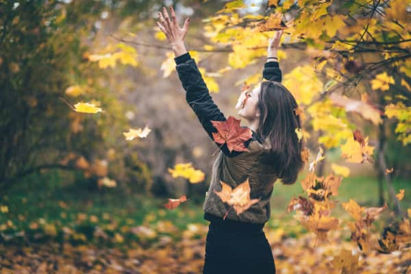 Young woman playing with yellow leaves in park.