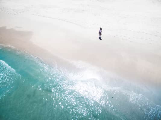 Lonely person standing on beach shore