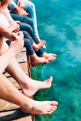 Close shot of legs family spending time together sitting on jetty over the lake in the summertime