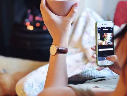 A woman lying on a sofa, drinking tea and taking pictures on her phone