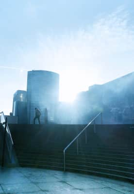 Man in bright sunlight, in the city, urban life and modern architecture, cityscape, silhouette, stairs, exploring, blue fog, blue sky, copy space