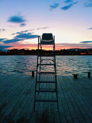 High chair for a gorgeous view on the bay at sunset, colorful sky, city skyline, waterfront, deck, light and shadows, copy space