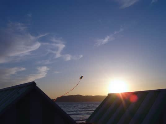 Kite, at the beach, at sunset, cabins, bright sunlight, horizon over the sea, blue sky, background, copy space