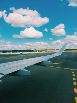 Summertime : airplane on the tarmac, ready for departure, blue sky, horizon over land, airplane wing, sunny day, white clouds, traveling, background, natural light, copy space