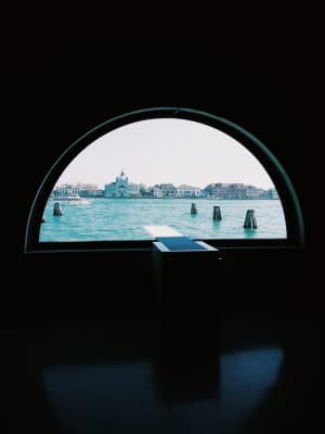 Secret Venice, Italy, view of the city skyline through a large window, lagoon and Giudecca island and canal, cityscape, city life, Redentore church, boat, sunny day, light and shadows, copy space