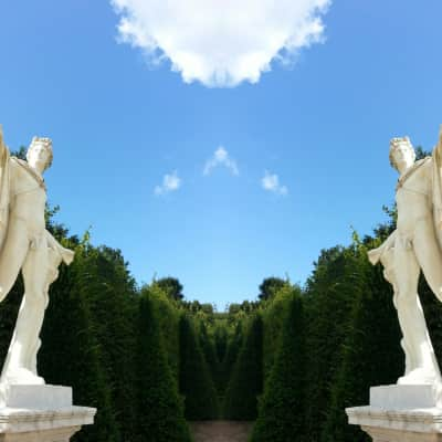 Two male statues in a Labyrinth, poetry, imagination, clear blue sky, white cloud, green trees, alley, garden, gods, sunny day, natural light, outdoors, copy space