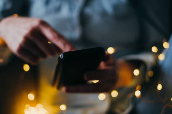 Woman using mobile phone at Christmas lights