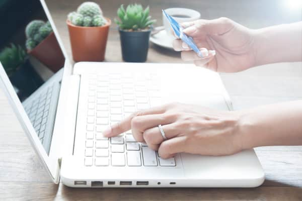Hand using laptop computer and holding credit card, Online shopping concept