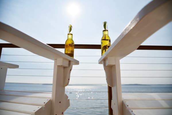 Blue Skies and Beers low angle bottles on deck chairs by the sea. RLTheis
