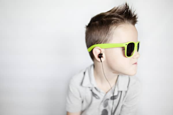portrait of boy on iPhone listening to music and dancing in headphones against a white background