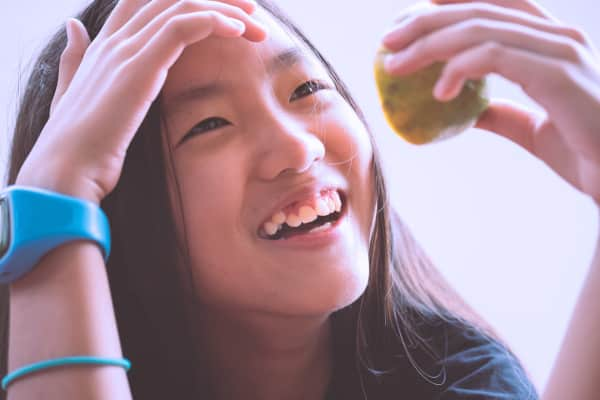 Overhead shot of an asian girl smiling happily while holding half sliced orange in her hand