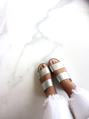 Bold metallic silver sandals worn by woman against white marble floor in minimalist setting.