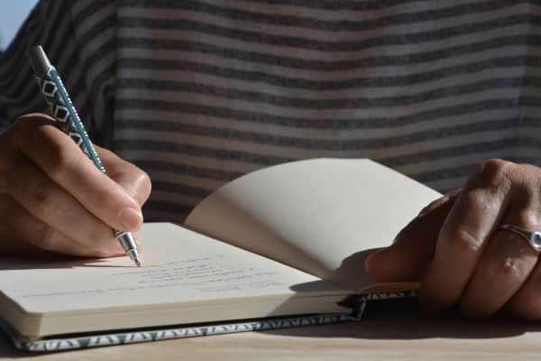 Woman writing in lined notebook, pen in hand, selective focus on pen nib