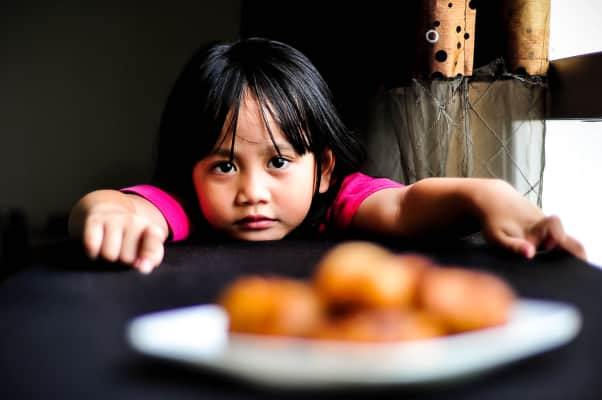 A young girl is looking cute in front of the food.