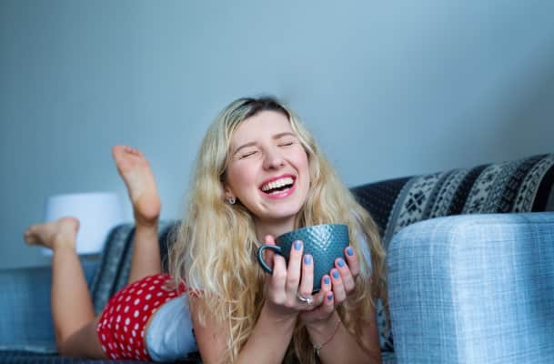 Coffe. cute blonde lies on the bed, drinks coffee and laughs