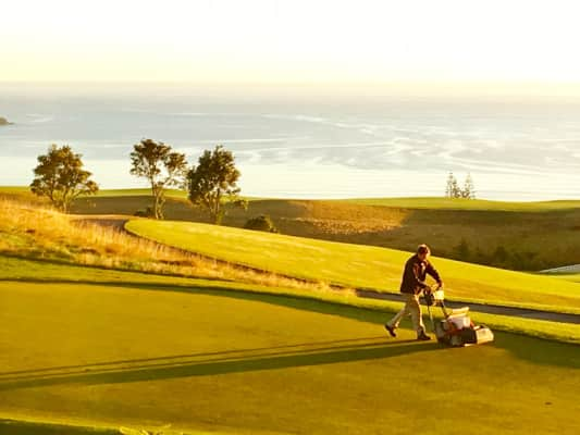 The Golden Hour: Early morning greenskeeper at work. Kauri Cliffs on the ocean. NZ