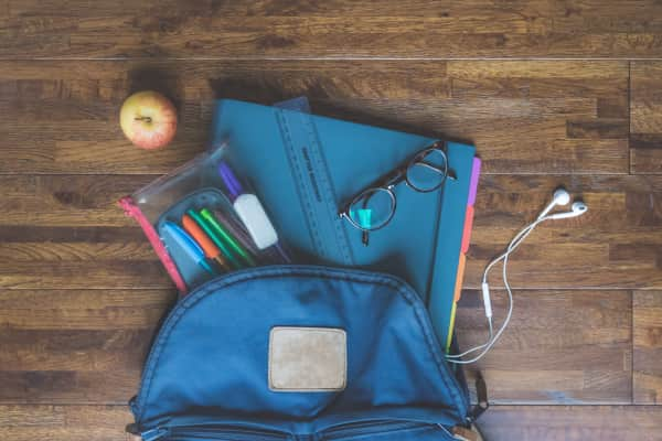 Backpack with pencil case, apple, stationary, earphones and glasses, ready for school