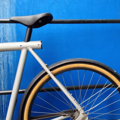 Detail of bicycle parked in front of a blue wall.