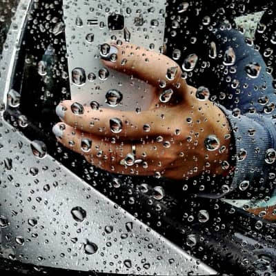 Rainy day. Women using mobile device, taking photos in the rain while driving.  Mirror reflexion. Car and phone, travel items water drops