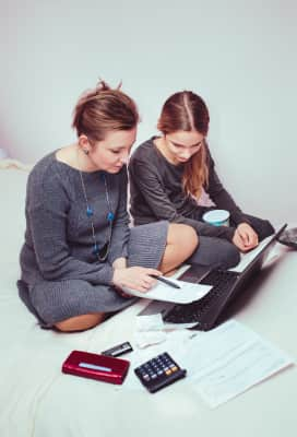 Woman and her daughter planning budget at home. Working at home. Doing things remotely