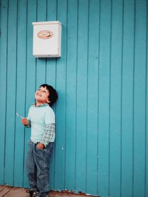 Smiling and happy kid in joyous moment having lollipop in hand and standing by pale blue wooden wall.