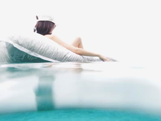 Woman floating in the pool on an inflatable