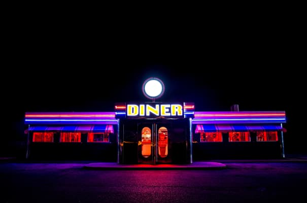 A traditional American Diner at night with a large sign and clorful luminous, fluourescent and neon lighting that glows in the dark.
