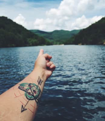 Tattoo arm  pointing to mountains across the distance over water