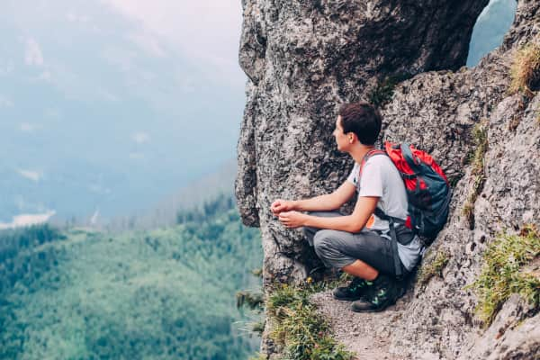 Summer vacation in the mountains. Young man admiring beauty of nature sitting on a rock. Boy resting on a rock in the Tatra Mountains