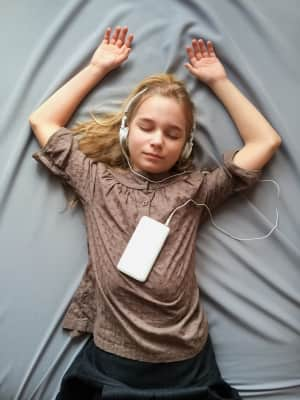 Teenager listening to music using smartphone and headphones. Girl with closed eyes lying on a bed. It sounds like a dream