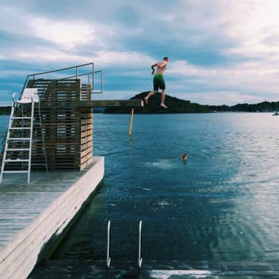 Guys jumping in the bay from a diving board, by the sea, horizon over the sea, leisure time, fun