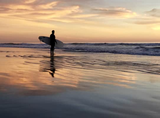 Surfer watching his son surfing at sunset.