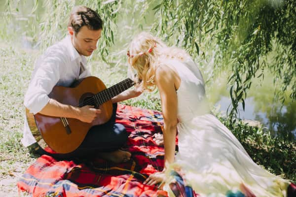 Lovers playing guitar on the grass