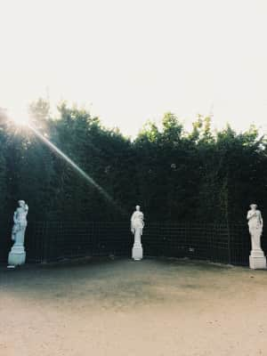 Three statues in a garden, green plants, sunlight and sunbeam, sun ray, copy space, Mystery and Poetry of the Versailles gardens